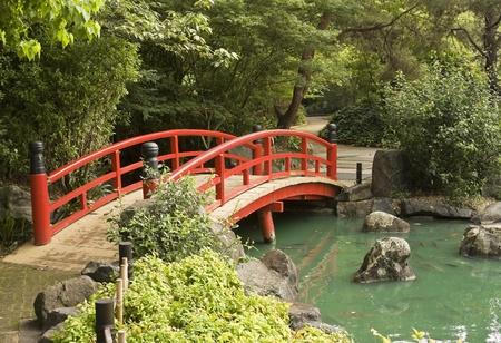 Foto de A red wooden bridge over a pond in a Japanese garden - Imagen libre de derechos