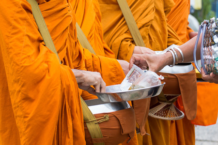 Buddhist monk of Thailand while stand in a row waiting people put rice and food offerings in their alms bowl for make merit