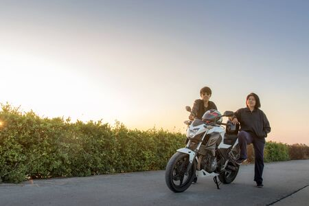 Photo pour Asian man and woman with helmet and wearing and fasten before riding big bike motorcycle on the road for safety - image libre de droit