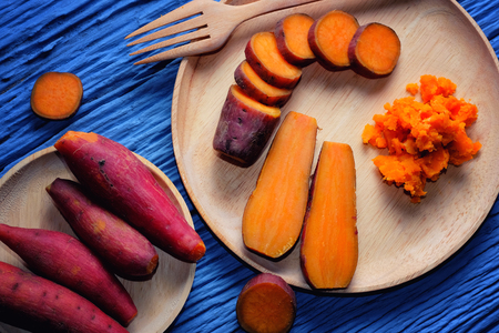 Sweet Potato on wooden cutting board with blue wood background
