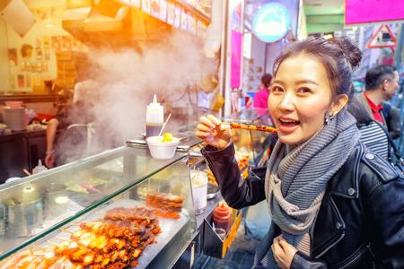 Foto de Chinese Asian young female model eating Grilled octopus on Street in Hong Kong - Imagen libre de derechos