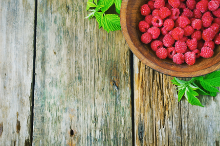 tasty ripe raspberries in wooden bowl on the old wooden background