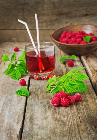 drink of fresh raspberries and ripe raspberry on the old wooden table