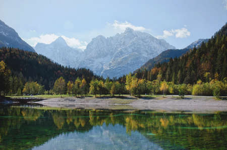 Photo pour Autumn alps mountains in day light reflected in calm waters of lake. - image libre de droit