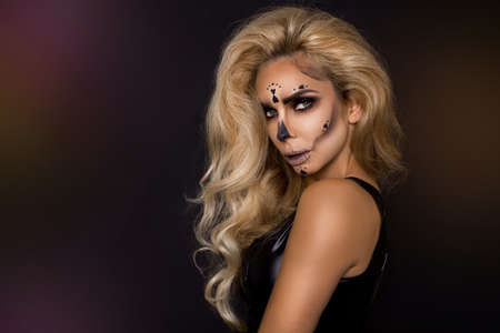 Photo for Sexy blonde woman in Halloween makeup and leather outfit on a black background in the studio. Skeleton, monster - Royalty Free Image