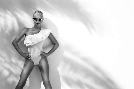 Photo pour Elegant sexy blonde model in elegant white bikini on amazing view with palm tree shadow in Cannes, France. Bikini model concept. Elegance. Black and white photo. - image libre de droit