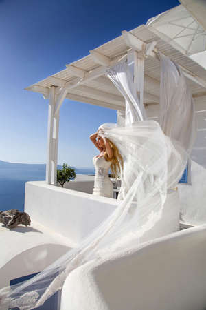 Photo pour Romantic beautiful bride in white dress posing on terrace with sea and mountains in background. Bride in Santorini island. Bride, wedding concept. - image libre de droit