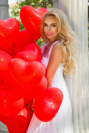 Photo pour Bride in a wedding dress is walking in a beautiful garden and holding red balloons. Set of Air Balloons. Wedding fashion. Valentines day and bride at the wedding party. - image libre de droit