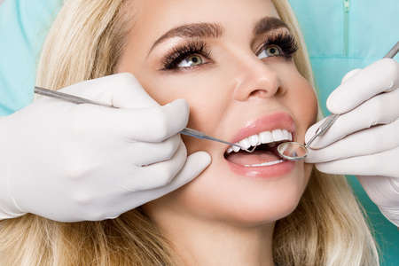 Photo pour Porcelain veneers. Pretty female model with perfect smile. Young beautiful woman with beautiful white teeth sitting on a dental chair. Teeth whitening. - image libre de droit