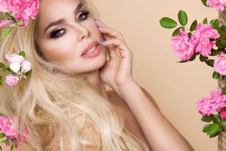 Foto de Portrait of a beautiful, smiling woman with long blonde hair and perfect makeup around the roses. Beauty face model. Spring makeup. Spring flowers concept. - Imagen libre de derechos