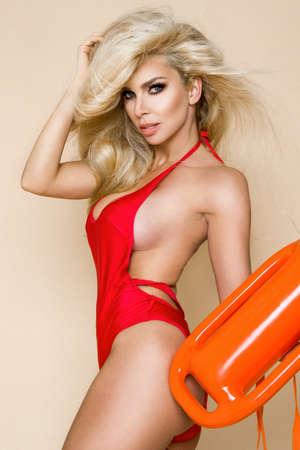 Photo pour Sexy busty blonde lifeguard woman with red bikini is holding lifeguard float on beige, pastel background and sensually posing. Bikini hot model. Sexy lifeguard. Bikini fashion. - image libre de droit