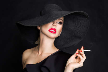 Foto de Sexy woman in elegant hat and with red lips blowing smoke, isolated on black. Femme fatale. Elegant lady with cigarette. - Imagen libre de derechos
