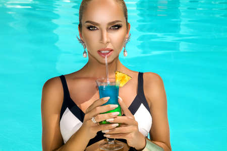 Photo pour Beautiful young woman with perfect skin and trendy nails is posing in pool with colorful drink. Portrait of beauty model with summer makeup and elegant manicure. Spa, skincare and wellness. - image libre de droit