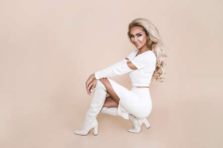 Photo pour Winter fashion model in studio. Beautiful lady in white outfit and white boots. Winter beauty in luxury. Fashion model posing in winter outfit - Image - image libre de droit