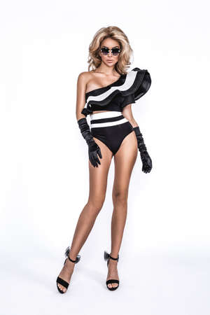 Photo for Bikini fashion. Elegant tanned woman in a black and white bikini and sunglasses isolated on white background in studio. Swimsuit fashion. Elegance. Summer fashion. - Royalty Free Image