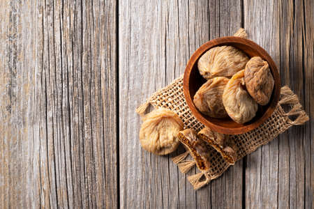 Photo pour A view from above of dried figs in a wooden bowl set against an old wooden background - image libre de droit