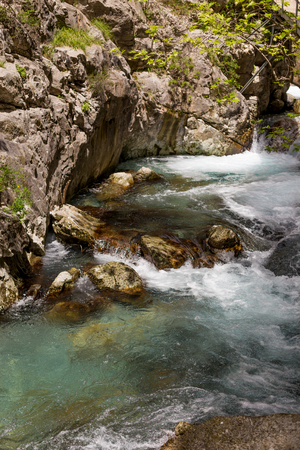 Vertical shot of a powerful water stream in the mountain river canyon with crystal clear water.