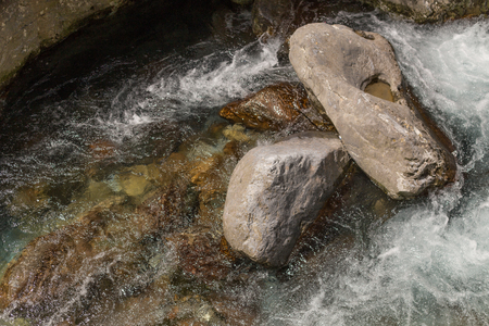 Closeup shot of powerful water stream in the mountain river.
