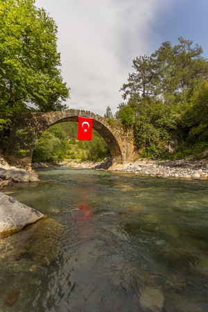 Old stone bridge over the mountain river with crystal clear water and the flag of Turkey hanging from that bridge. Vertical composition.