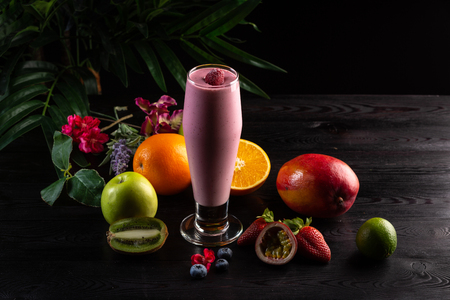 Pink smoothie in a tall glass and fruits on a dark wooden background