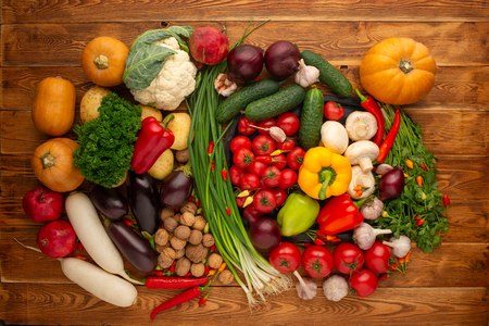 Photo pour Fresh vegetables and nuts on a brown wooden background - image libre de droit