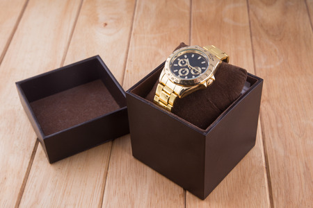 box with luxury watch on wooden background