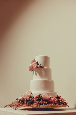 Photo pour White wedding cake decorated with  roses on the table. - image libre de droit