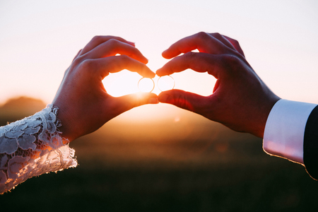Photo for Two married people holding wedding rings at sunset. - Royalty Free Image
