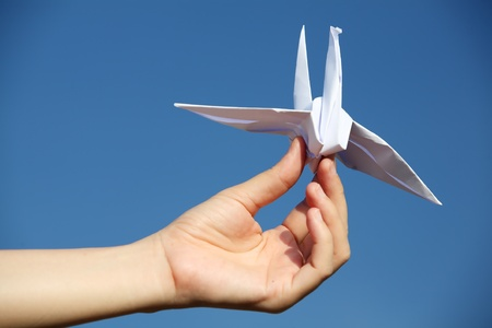 hand holding origami bird.