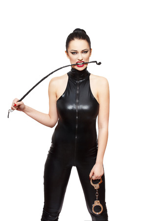 Sexy dominatrix with whip and handcuffs, isolated on white background