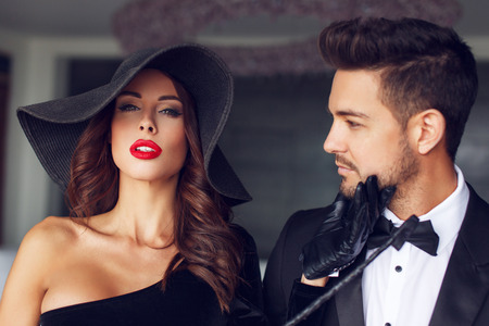 Photo pour Sexy milf woman in hat with young lover in tuxedo in luxury flat - image libre de droit