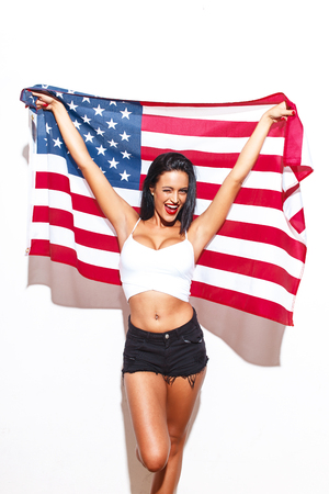 Sexy woman with big tits and USA flag at wall, 4th of July