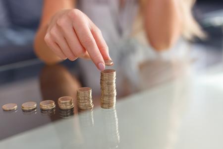 Photo pour Woman hands build coin columns on glass desk closeup - image libre de droit