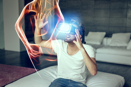 Photo pour Young man with VR headset playing with fiery virtual sexy woman silhouette - image libre de droit