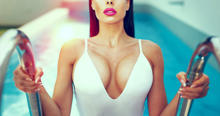 Photo pour Sexy wet woman with big titis at swimming pool in sunset, color graded - image libre de droit