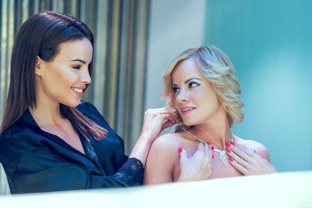 Photo pour Young 20s lesbian rich women looking each other at mirror - image libre de droit