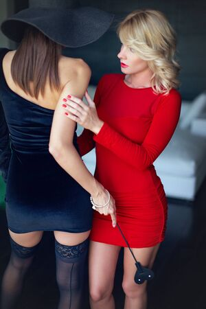 Photo pour Blonde woman in red with lesbian lover foreplay by whip, seduction - image libre de droit