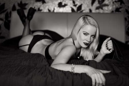 Photo pour Sexy blonde woman in underwear posing on bed in bedroom, black and white - image libre de droit