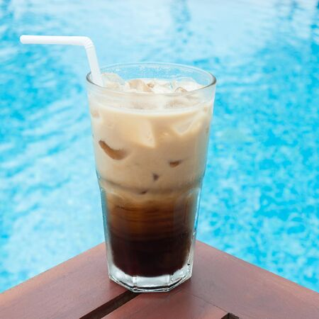 Iced coffee on the table beside the pool