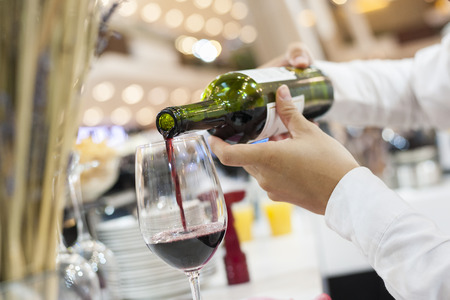 Photo pour Red wine pouring into a wine glass with bokeh on background - image libre de droit