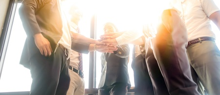 Photo pour Business people join hand together during their meeting with sun rays aura background. - image libre de droit