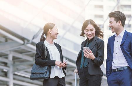 Photo pour Group of Asian business colleagues using mobile phone's outside the office. - image libre de droit