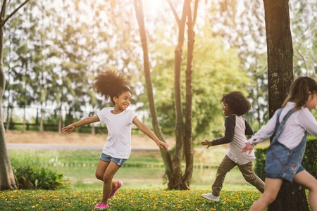 Foto de Cute african american little girl playing outdoor - Black people kid and friend happy. - Imagen libre de derechos