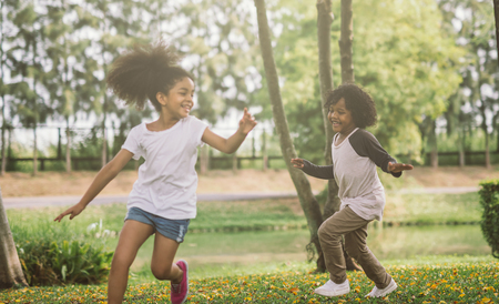 Foto de Kids playing with friends. Children Running At Park - Imagen libre de derechos