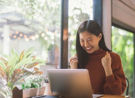 Foto de Young Asian woman celebrate success or happy pose with laptop - Imagen libre de derechos