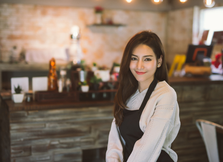 Photo pour Portrait of Asian girl waitress wearing apron and standing in coffee shop. - image libre de droit