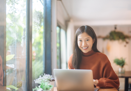 Photo pour Happy young Asian girl working at a coffee shop with a laptop looking at camera. - image libre de droit