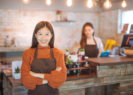 Photo pour Portrait of Asian girl waitress holding menu wearing apron and standing in coffee shop. - image libre de droit