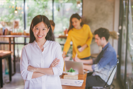 Foto de Portrait of asian female leader of working team coworking office ,Smiling of happy chinese girl in modern office - Imagen libre de derechos
