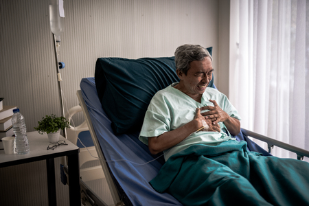 Photo pour Mature man with chest pain suffering from heart attack in hospital bed. - image libre de droit